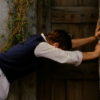 Peter pushing the wall aside to reveal a door